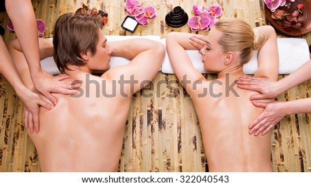 Beautiful couple getting deep back massage and relaxation at the spa salon. - stock photo
