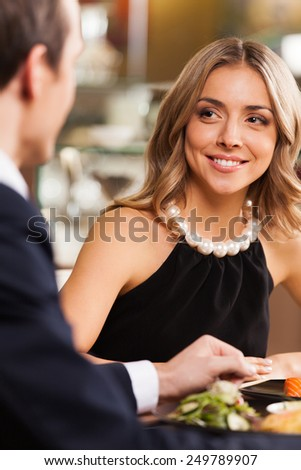 Beautiful couple having romantic dinner at restaurant. smiling woman looking at man at cafe sitting at table - stock photo