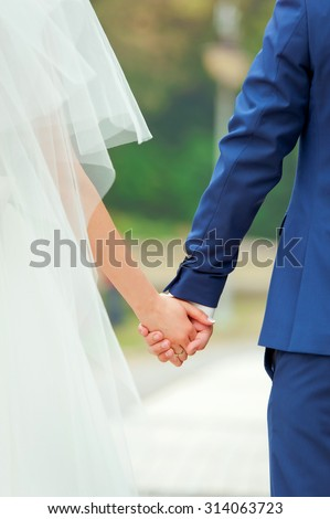 Beautiful couple holding hands. Back view. Bride and groom. - stock photo