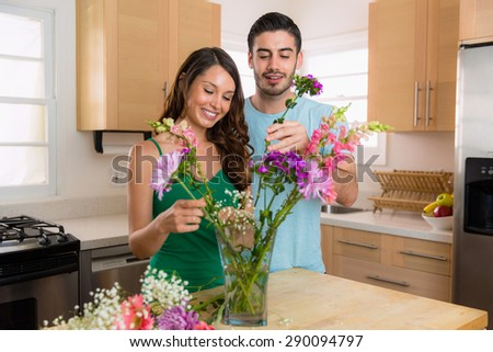 Beautiful couple in a relationship share flowers at home in the summer - stock photo