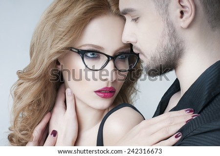 Beautiful couple in love. Blond woman hugging a man. Woman wearing eyeglasses.  Passionate couple in love. Portrait of  beauty girl and her handsome boyfriend. Love. Kiss. Flirt.  Lovers.  - stock photo