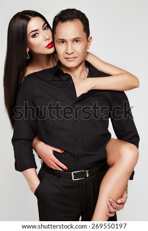 Beautiful couple in love brunette girl with long hair red lipstick and jewelery naked hugs sexual brutal handsome man in a black shirt and suit tenderness and passion - stock photo