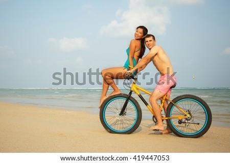 Beautiful couple in love enjoying life on the beach of tropical island. Riding a stylish bike with fat wheels. Wearing stylish blue bikini, pink shorts. Interracial couple, Asian woman, Caucasian man - stock photo