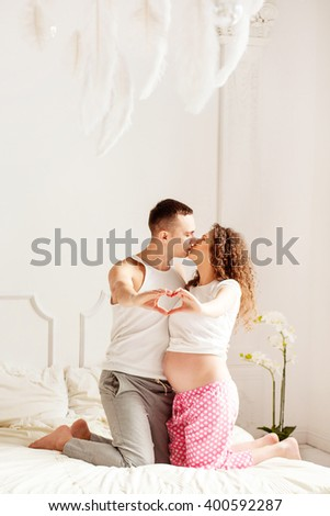Beautiful couple in love in the bedroom. They kiss. She is pregnant and standing on the bed. A man stands next to. They laid down their arms in the shape of a heart. Both dressed in home clothes. - stock photo