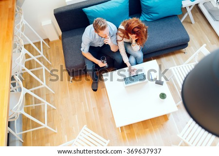 Beautiful couple in love working in a cosy living room - stock photo