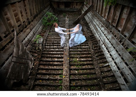 beautiful couple in the old boat in wedding dress - stock photo