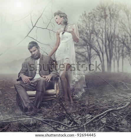 Beautiful couple in winter scenery - stock photo