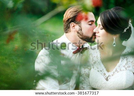 Beautiful couple kissing among spring foliage. Close up portrait of bride and groom at wedding day outdoor, lit by setting sunlight. Man with bow tie and suspenders, woman in  white dress. Copy space. - stock photo