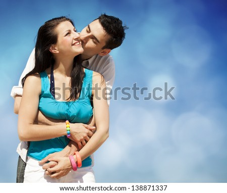 Beautiful couple kissing on blue sky background. Photo with bokeh at background - stock photo