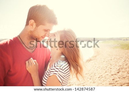 beautiful couple kissing on the beach on a sunny morning - stock photo