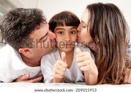 Beautiful couple kissing the child - stock photo