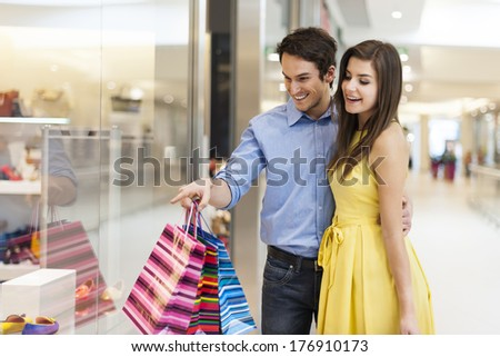 Beautiful couple looking at window shopping  - stock photo
