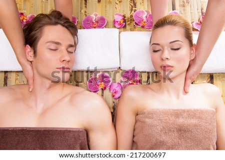 Beautiful couple lying in a spa salon enjoying head massage together. - stock photo