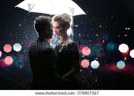 Beautiful couple man with woman  with  white umbrella in flash lights and rain drops - stock photo