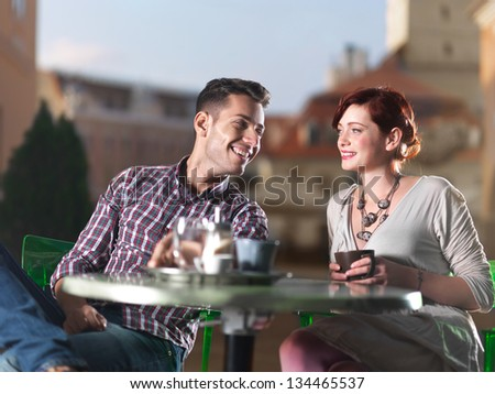 beautiful couple on coffee on the terrace in the town square at sunset - stock photo