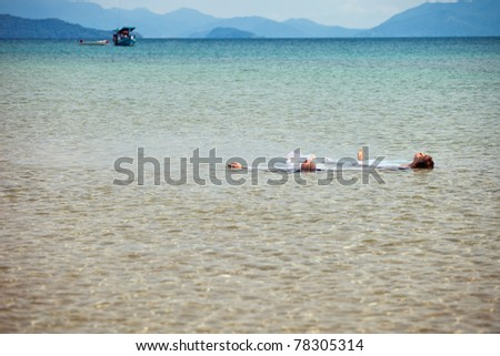 beautiful couple on the beach in wedding dress lying in the water - stock photo