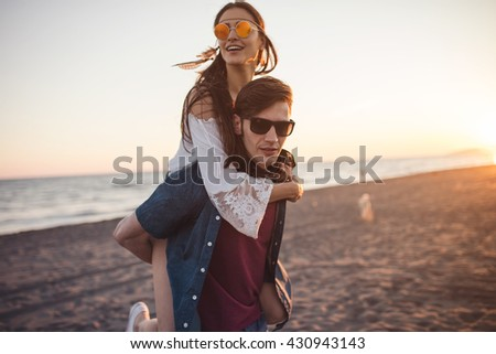 Beautiful couple on the beach. Piggyback ride. Depth of field, focus only on man's face. Happy friends, summer vacation, summer concept  - stock photo