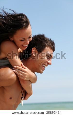 beautiful couple posing on the sandy sea coast - stock photo