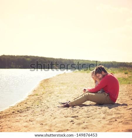 Beautiful couple sitting on the beach - stock photo