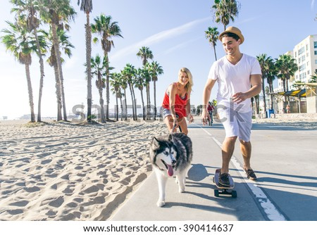 Beautiful couple skating with dog on ocean walk front during a summer vacation - Cheerful happy friends doing sport activity on the beach - stock photo