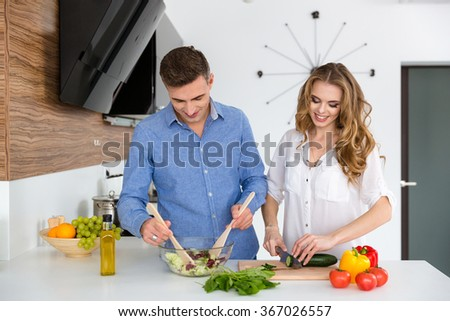 Beautiful couple standing and cooking healthy food together on the kitchen - stock photo