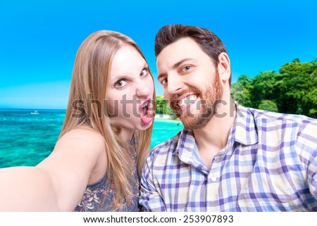 Beautiful Couple taking a selfie photo on the beach - stock photo
