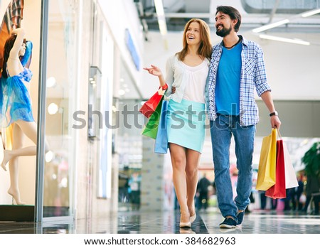 Beautiful couple walking through the mall and carrying shopping bags - stock photo