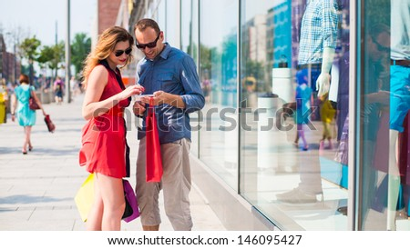 beautiful couple walking through the mall carrying a lot of shopping bags. In the background window dressing.  - stock photo