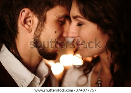 Beautiful Couple with Closed Eyes Enjoying Kissing and Embrassing One Another. Close Up Headshot, Selective Focus. - stock photo