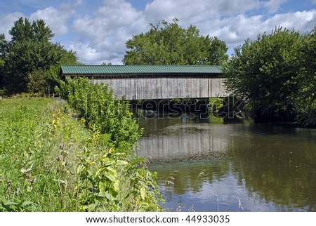 Beautiful  covered bridge across a lazy  river in Vermont with vegetation in foreground and partly cloudy sky in background. - stock photo