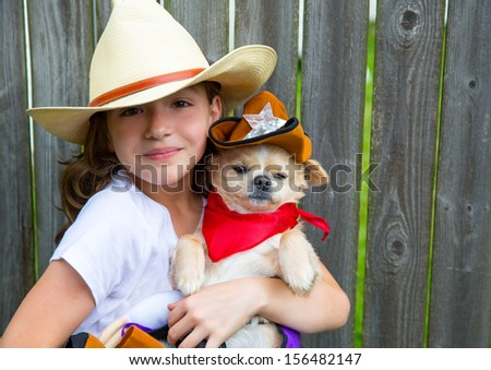 Beautiful cowboy kid girl holding chihuahua dog with sheriff hat in backyard wooden fence - stock photo