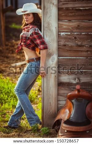 beautiful cowgirl style model posing with saddle on farmland - stock photo