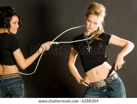 Beautiful cowgirls in action, one is drawing in a lasso to capture the other who is drawing a gun. - stock photo