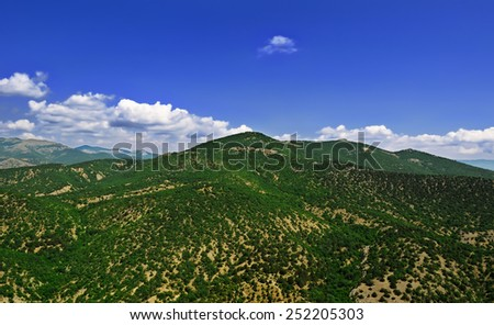 Beautiful Crimean landscape - low mountains with vegetation and a blue sky with clouds in the distance - stock photo
