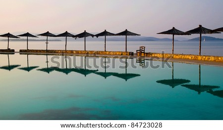 Beautiful croatian beach with pool and umbrellas - stock photo