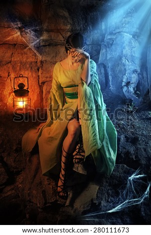 Beautiful crying princess in the dark dungeon with the spiders - stock photo