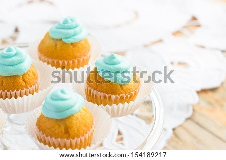 beautiful cupcakes decorated with turquois frosting. Selective focus - stock photo