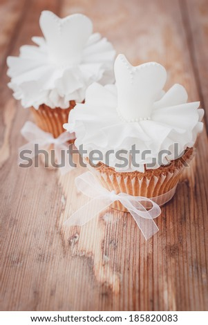 Beautiful cupcakes for wedding or little ballerina. Decorated with white sugar paste dresses. Selective focus - stock photo