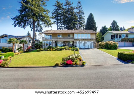 Beautiful curb appeal of two story house with beige exterior paint. Nice front garden with well kept lawn and trimmed hedges  - stock photo
