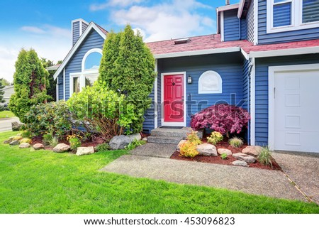 Beautiful curb appeal with blue exterior paint and red roof. Nice front landscape design. - stock photo