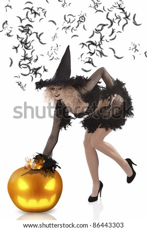 beautiful curled blonde wearing a black feathered witch costume and high heels - stock photo