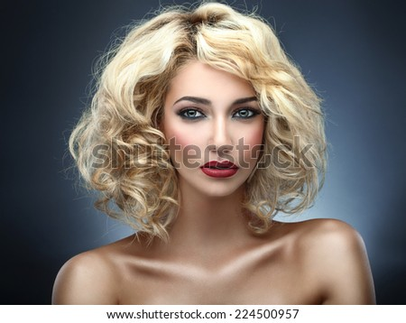Beautiful curly blonde (blue background) - stock photo