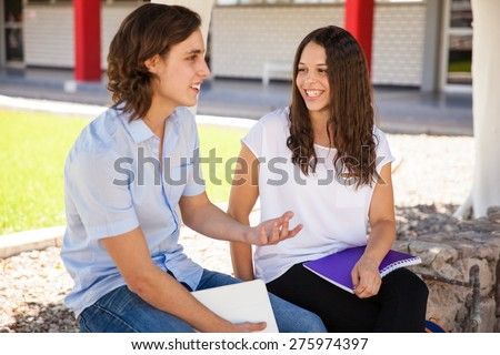 Beautiful curly brunette enjoying her talk with the guy she likes at school - stock photo