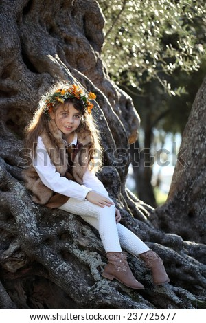 Beautiful curly girl with floral wreath on his head. Cute child in a stylish dress sitting on an olive tree. - stock photo