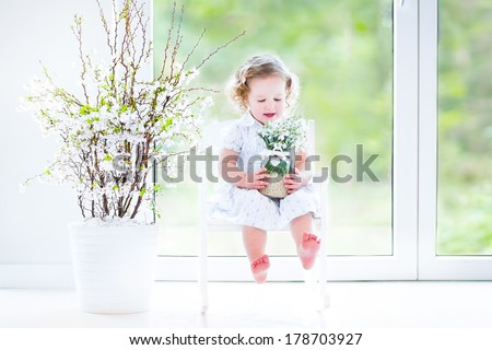 Beautiful curly toddler girl in a white dress sitting in a white rocking chair next to a big garden view window holding first spring flowers in a transparent crystal vase - stock photo