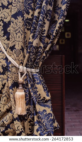Beautiful curtain with a tassel in a fashionable apartment - stock photo