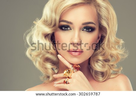 Beautiful cute girl with blonde curly hair with large rings on her  hand - stock photo