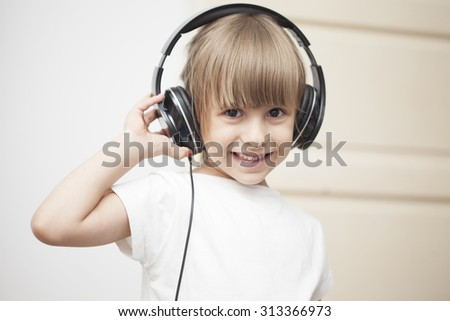 Beautiful cute happy  girl with headphones grooving having fun listening to music, isolated. - stock photo