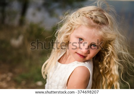 beautiful cute little child with long blond hair - stock photo