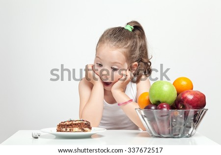 beautiful cute little girl with open mouth looking at cake hungrily - stock photo